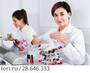 Купить «Female manicurist showing lacquer color schemes», фото № 28646333, снято 2 февраля 2017 г. (c) Яков Филимонов / Фотобанк Лори