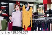 Купить «Glad female deciding on pretty blouse», фото № 28646337, снято 7 февраля 2017 г. (c) Яков Филимонов / Фотобанк Лори