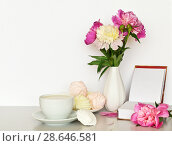 Купить «Still life with fresh peonies in a vase, open book, a cup of milk drink and vanilla marshmallow on a light table. Free space for text», фото № 28646581, снято 27 июня 2018 г. (c) Виктория Катьянова / Фотобанк Лори