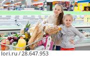 Купить «Two girls are standing with cart with products in the supermarket.», фото № 28647953, снято 4 апреля 2018 г. (c) Яков Филимонов / Фотобанк Лори