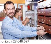 Купить «Young man choosing postbox for his home in specialty workshop», фото № 28648097, снято 17 апреля 2018 г. (c) Яков Филимонов / Фотобанк Лори