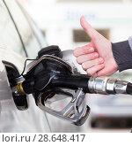 Купить «Petrol or gasoline being pumped into a motor vehicle car. Closeup of man, showing thumb up gesture, pumping gasoline fuel in car at gas station.», фото № 28648417, снято 30 апреля 2014 г. (c) Matej Kastelic / Фотобанк Лори