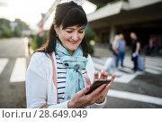 Весёлая женщина средних лет набирает номер на телефоне. Стоковое фото, фотограф Игорь Низов / Фотобанк Лори