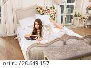 Young woman wearing chemise and peignoir reads a book. Стоковое фото, фотограф Сергей Дубров / Фотобанк Лори