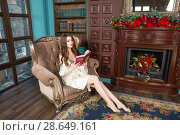Купить «Young woman wearing chemise and peignoir sits in a arm-chair in living room and reads a book», фото № 28649161, снято 1 апреля 2018 г. (c) Сергей Дубров / Фотобанк Лори
