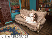 Lass wearing nightwear lies on sofa in library and reads a book (2018 год). Редакционное фото, фотограф Сергей Дубров / Фотобанк Лори