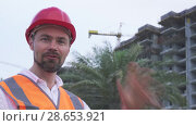 Man in a helmet, architect, engineer, manager tells about the progress of construction in evening stock footage video. Стоковое видео, видеограф Юлия Машкова / Фотобанк Лори