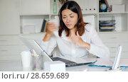Купить «Worried female doctor working at laptop with papers in her office», видеоролик № 28659689, снято 23 мая 2018 г. (c) Яков Филимонов / Фотобанк Лори