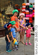 Купить «2018 FIFA World Cup. Children in souvenir hats near gift shop on Nikolskaya street in center of Moscow», фото № 28660713, снято 30 июня 2018 г. (c) Валерия Попова / Фотобанк Лори