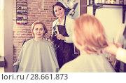 Купить «Young woman decides with master how to cut hair», фото № 28661873, снято 7 марта 2017 г. (c) Яков Филимонов / Фотобанк Лори