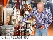 Купить «Portrait of mature man choosing vintage goods at antiques shop», фото № 28661893, снято 15 мая 2018 г. (c) Яков Филимонов / Фотобанк Лори