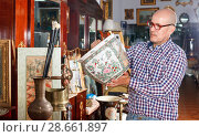 Купить «Portrait of mature man choosing vintage goods at antiques shop», фото № 28661897, снято 15 мая 2018 г. (c) Яков Филимонов / Фотобанк Лори