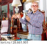 Купить «Portrait of successful owner of antiques shop among vintage things», фото № 28661901, снято 15 мая 2018 г. (c) Яков Филимонов / Фотобанк Лори