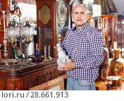 Купить «Portrait of successful owner of antiques shop among vintage things», фото № 28661913, снято 15 мая 2018 г. (c) Яков Филимонов / Фотобанк Лори