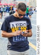 Купить «Турист в футболке AERO NYC 1987 со смартфоном в руках гуляет по Красной площади. Москва», фото № 28663641, снято 29 июня 2018 г. (c) Алёшина Оксана / Фотобанк Лори