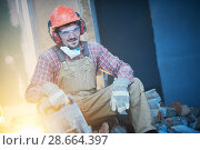 Купить «breaking interior wall. worker portrait with demolition hammer», фото № 28664397, снято 9 декабря 2017 г. (c) Дмитрий Калиновский / Фотобанк Лори