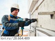 Купить «builder installing bracket on building facade wall», фото № 28664489, снято 20 февраля 2018 г. (c) Дмитрий Калиновский / Фотобанк Лори