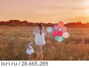 Купить «happy mother and daughter with balloons at sunset», фото № 28665289, снято 10 августа 2017 г. (c) Майя Крученкова / Фотобанк Лори
