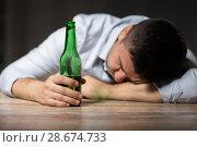 Купить «drunk man with beer bottle lying on table at night», фото № 28674733, снято 24 ноября 2017 г. (c) Syda Productions / Фотобанк Лори