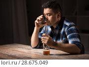 Купить «alcoholic with bottle drinking whiskey at night», фото № 28675049, снято 24 ноября 2017 г. (c) Syda Productions / Фотобанк Лори