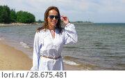 Купить «happy smiling woman walking along summer beach», видеоролик № 28675481, снято 25 июня 2018 г. (c) Syda Productions / Фотобанк Лори