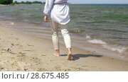 woman walking barefoot along beach. Стоковое видео, видеограф Syda Productions / Фотобанк Лори