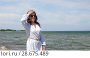 Купить «happy smiling woman walking along summer beach», видеоролик № 28675489, снято 25 июня 2018 г. (c) Syda Productions / Фотобанк Лори