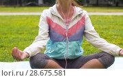 Купить «woman with earphones meditating at park», видеоролик № 28675581, снято 25 июня 2018 г. (c) Syda Productions / Фотобанк Лори