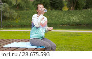 Купить «woman drinking water after exercising in park», видеоролик № 28675593, снято 25 июня 2018 г. (c) Syda Productions / Фотобанк Лори