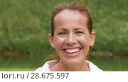 Купить «portrait of smiling middle-aged woman in park», видеоролик № 28675597, снято 27 июня 2018 г. (c) Syda Productions / Фотобанк Лори
