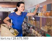 Купить «female customer choosing natural dried berries sold by weight in eco market», фото № 28675989, снято 13 июня 2017 г. (c) Яков Филимонов / Фотобанк Лори