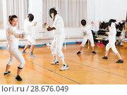 Купить «Young woman fencer practicing effective fencing techniques in training room», фото № 28676049, снято 30 мая 2018 г. (c) Яков Филимонов / Фотобанк Лори