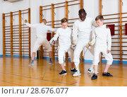 Купить «Focused boys fencers attentively listening to professional fencing coach in gym», фото № 28676077, снято 30 мая 2018 г. (c) Яков Филимонов / Фотобанк Лори