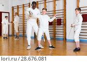 Купить «Fencing instructor with young fencers in training room», фото № 28676081, снято 30 мая 2018 г. (c) Яков Филимонов / Фотобанк Лори