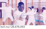 Купить «African American fencer practicing effective fencing techniques in training room», фото № 28676093, снято 30 мая 2018 г. (c) Яков Филимонов / Фотобанк Лори