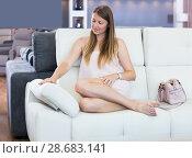 Купить «Adult woman sitting barefoot and testing sofa», фото № 28683141, снято 5 сентября 2017 г. (c) Яков Филимонов / Фотобанк Лори