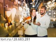Купить «Smiling couple customers choosing bedside lamp in furniture stor», фото № 28683281, снято 29 января 2018 г. (c) Яков Филимонов / Фотобанк Лори
