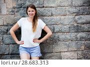 Купить «Young woman standing on stone wall background», фото № 28683313, снято 15 августа 2017 г. (c) Яков Филимонов / Фотобанк Лори