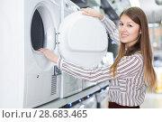 Купить «Young female housewife choosing new washer», фото № 28683465, снято 12 декабря 2017 г. (c) Яков Филимонов / Фотобанк Лори