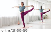 Купить «woman doing yoga hand-to-big-toe pose at studio», видеоролик № 28683693, снято 28 июня 2018 г. (c) Syda Productions / Фотобанк Лори