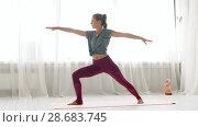 Купить «woman doing yoga warrior pose at studio», видеоролик № 28683745, снято 28 июня 2018 г. (c) Syda Productions / Фотобанк Лори