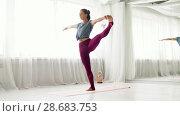 Купить «woman doing yoga hand-to-big-toe pose at studio», видеоролик № 28683753, снято 28 июня 2018 г. (c) Syda Productions / Фотобанк Лори