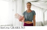 Купить «happy woman with exercise mat at yoga studio», видеоролик № 28683761, снято 28 июня 2018 г. (c) Syda Productions / Фотобанк Лори
