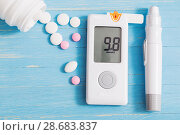Купить «glucometer and pills on blue wooden background», фото № 28683837, снято 3 июля 2018 г. (c) Майя Крученкова / Фотобанк Лори