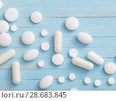 Купить «white pills on blue wooden background», фото № 28683845, снято 3 июля 2018 г. (c) Майя Крученкова / Фотобанк Лори