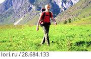 Купить «Hiking man walking on green mountain meadow with backpack. Summer sport and recreation concept.», видеоролик № 28684133, снято 17 апреля 2018 г. (c) Александр Маркин / Фотобанк Лори