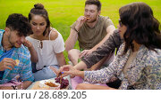 Купить «friends with drinks eating food at summer picnic», видеоролик № 28689205, снято 26 июня 2018 г. (c) Syda Productions / Фотобанк Лори