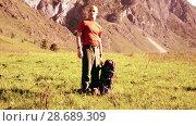 Купить «Hiking man walking on green mountain meadow with backpack. Summer sport and recreation concept.», видеоролик № 28689309, снято 18 апреля 2018 г. (c) Александр Маркин / Фотобанк Лори