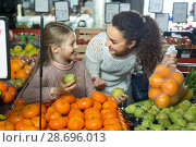 portret of young woman with beautiful blonde daughter choosing mandarins at store. Стоковое фото, фотограф Татьяна Яцевич / Фотобанк Лори