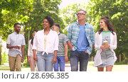 Купить «international friends with coffee walking in park», видеоролик № 28696385, снято 25 июня 2018 г. (c) Syda Productions / Фотобанк Лори